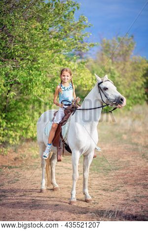 Schoolgirl Girl Rides A White Pony. The Child Is Riding A Horse. Horse Riding Training For Children.