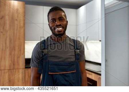 Happy Smiling African American Handyman In Overalls, Posing In Modern Kitchen Interior, Smiling Look