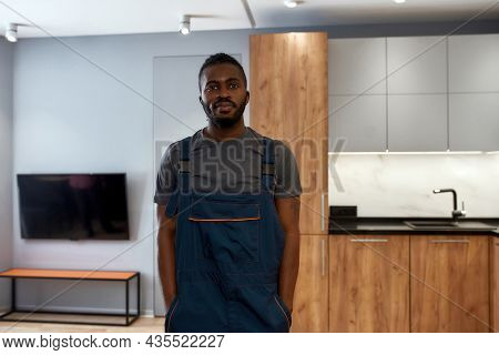 Portrait Of Handsome African American Man In Overalls, Posing In Appartment Interior, Holding Hands