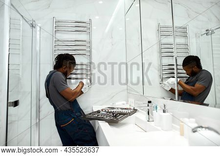 Portrait Of Handsome Mixed-race Plumber In Overalls And White Gloves, Fixing Electric Towel Rail In