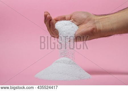 Washing Powder On A Pink Background. Detergent For Washing Clothes. Washing Powder Pouring Out Of A