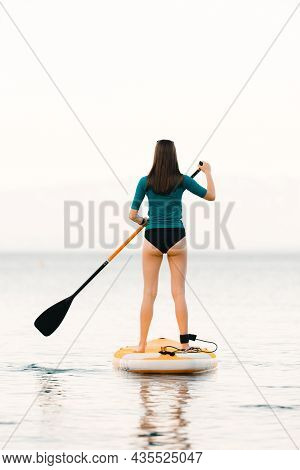 Young Girl On A Sup Board With A Paddle In Her Hand - Shot From The Back, Calm Surface Of The Sea -