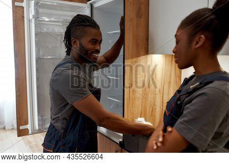 Portrait Of Young Stylish African American Handyman In Workwear Standing Near Opened Fridge Flirting