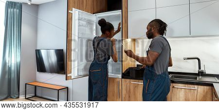 Back View Young Competent African Handyman Helping Young Unexperienced Repairwoman To Fix Fridge By