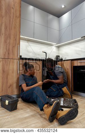 Skilled Male Plumber Checking Pipes Under Kitchen Sink, Female Apprentice Sitting Near, Passing Tool