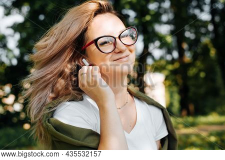 Portrait Of Smiling Young Woman Listening Audio On Wireless Portable Earphones, Teenage Girl In Red