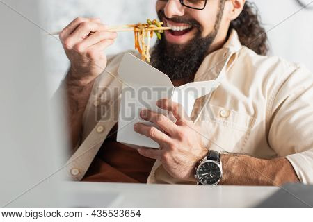 Partial View Of Bearded Man In Wristwatch Eating Chinese Noodles On Blurred Foreground