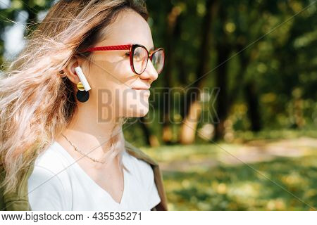 Profile Portrait Of Young Smiling Woman Listening Music With Portable Wireless Earphones Outdoors, C