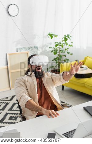 Astonished Hispanic Man Gesturing While Gaming In Vr Headset In Living Room
