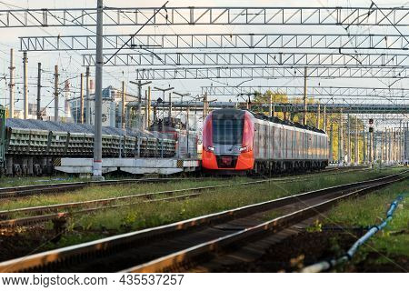 Front View Of Modern Russian Intercity High Speed Passenger Train On Railroad At Sunset, Freight Tra
