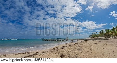 Background With Old Wooden Dock In Foreground And Modern Yachts In Background, On A Beach. Punta Can