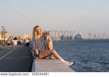 Melancholic Woman In 40s Enjoying Summer Sunset Sitting On River Embankment With Longboard Alone Aft
