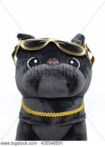 Portrait, Muzzle Of Dog Toy Closeup. Plush Soft Black Pug Dog Toy With Golden Sun Glasses And Gold C
