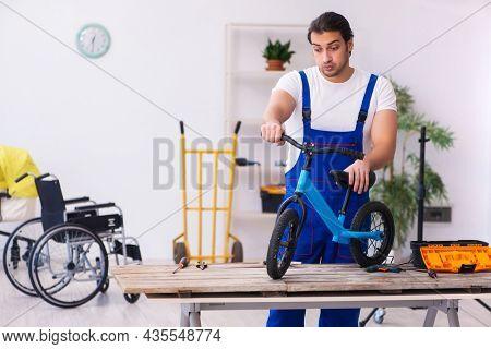 Young male repairer repairing bike indoors