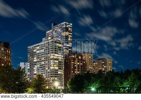 Long Exposure Of Clouds Moving Across A Dark Blue Sky Over Modern Residential Highrise Buildings In