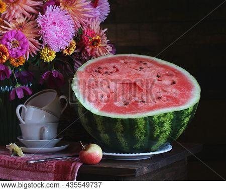 Half Of A Cut Ripe Watermelon Fragment Of A Still Life Flowers And Dishes On The Table
