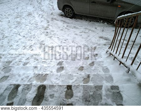 Footprints On Dirty Snowy Steps. Melted Snow. Winter Background. Snowfall In City. Frosty Cold Weath