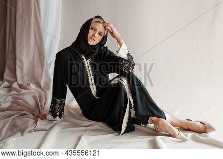 Beautiful Muslim Woman In Traditional Arabian Abaya Dress On Gray Background