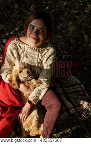 Young Woman Cuddling With Her Pet Dog, Covered With Red Blanket, Sitting Outdoors In The Forest, Dur