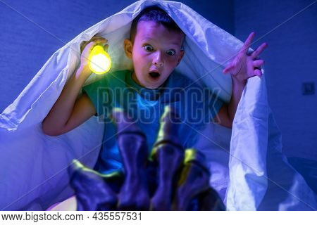 Scared Boy With A Flashlight Hides Under The Blanket From The Hand Of A Scary Monster. Nightmare For