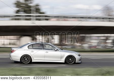 A Silver Car Is Driving On The Street At High Speed. Speeding In The City. Motion Blur. Riga, Latvia