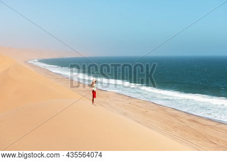 Single man in a cowboy hat in the Namib desert on Atlantic ocean background. Travel concept