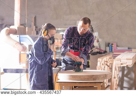 Experienced Carpenter Teaching Young Apprentice At Workshop