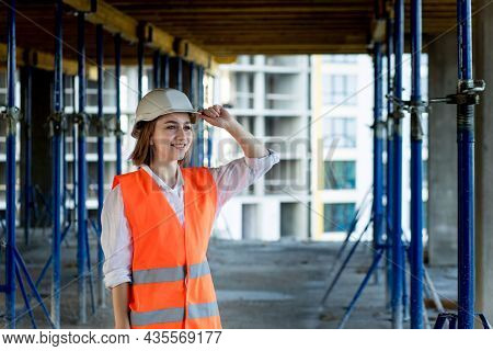 Portrait Of Beautiful Female Architect Who Stands Idly And Smiles Against The Background Of Building