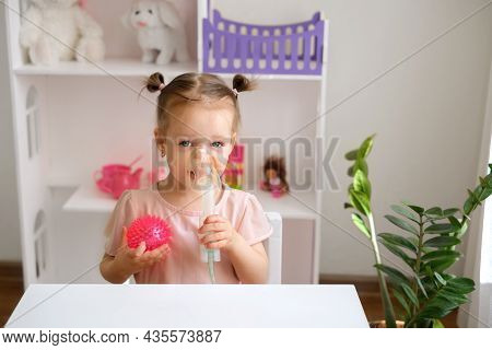 A Two-year-old Child Breathes Into An Inhalation Mask. Inhalations For Asthma, Bronchitis And Pneumo