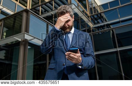 Nervous Entrepreneur In Businesslike Suit Looking At Phone Outside The Office, Anxiety