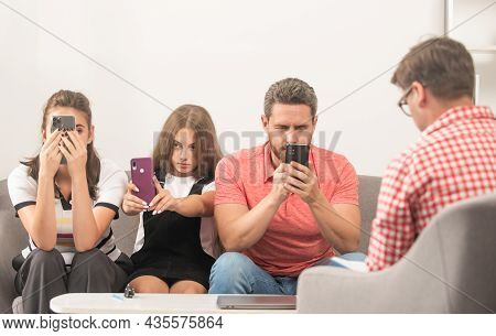 Family Therapy. Parents With Kid Talk To Social Worker. Phone Addicted Mom Dad And Daughter
