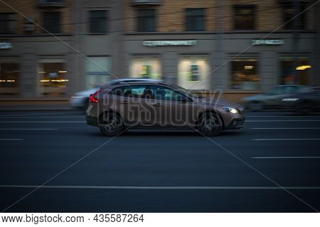 Side View Rolling Shot With Brown  Volvo V40 In Motion On City Street At Night. Evening Driving Alon