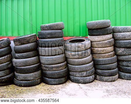 Old Tires Are Stacked Against The Wall. Close-up Of Worn Tires. A Pile Of Old Tires From Used Cars.