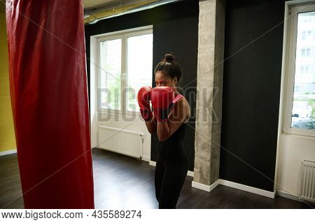 Fitness Woman Boxer In Tight-fitting Black Sportswear And Red Boxing Gloves Training In A Boxing Gym