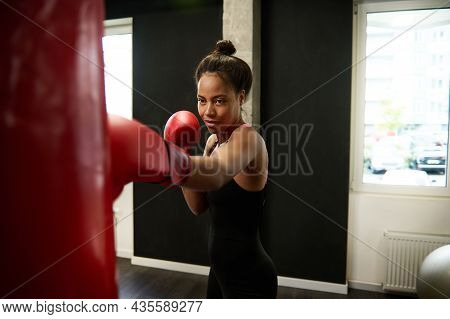 Beautiful African Athletic Woman, Boxer In Red Boxing Gloves, Trains Hard, Strikes A Straight Punch,