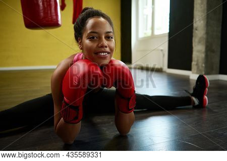 Front View Of Female Athlete, Woman Boxer In Boxing Red Gloves Performing A Twine On The Floor Of A
