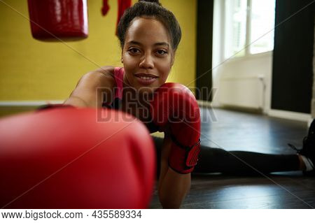 Young Smiling Beautiful Athletic Woman, Female Boxer In Red Boxing Gloves Stretches The Legs On The