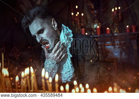 Bloodthirsty vampire baring his teeth among burning candles illuminating his dark gloomy castle at nighttime. Halloween.