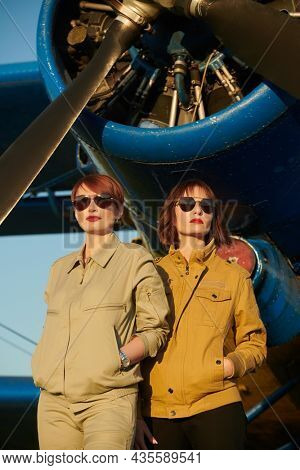 Aviation. Two professional female commercial aviation pilots in uniform and sunglasses standing in front of their plane.