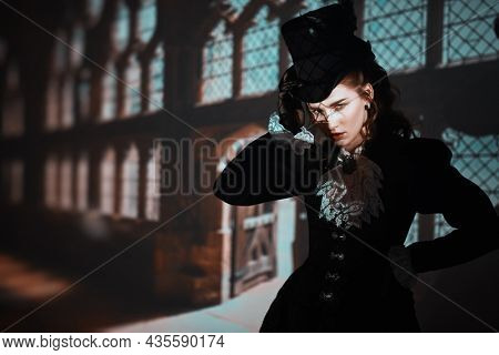 Historical reconstruction. Portrait of an elegant lady in a 19th century suit and hat posing at the railway station. Historical fashion and hairstyle. Steampunk lady.