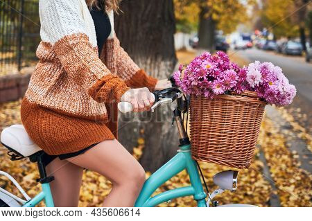 Close Up Of Female Bicyclist In Knitted Cardigan Riding Bike With Flowers On Autumn Street. Young Wo