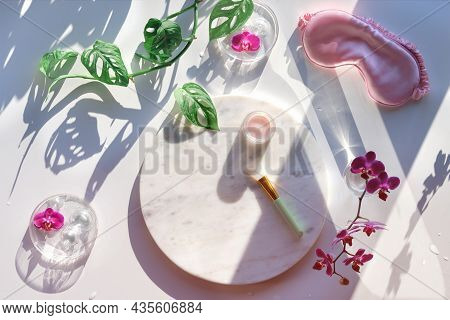 Moisturizing Cream On Marble Plate And Pink Silk Sleep Mask. Exotic Flat Lay With Monstera Leaves An