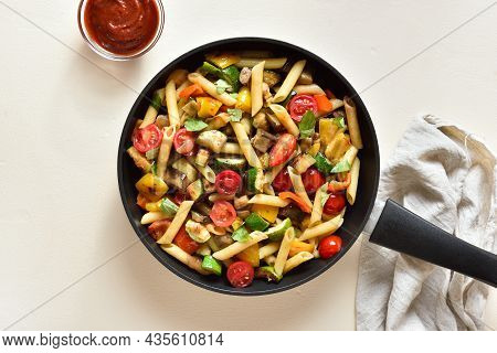 Tasty Appetizing Penne Pasta With Roasted Vegetables In Frying Pan Over Light Stone Background. Top