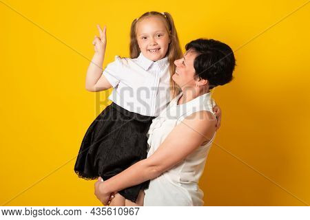 Photo Of Pretty Young Mommy Hold Arms Hugging Little Daughter Good Mood, Isolated Yellow Color Backg