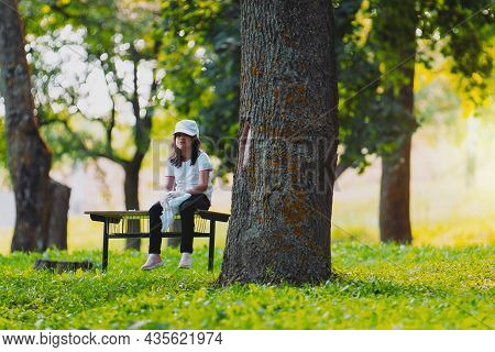 Close Up Photo Of A Beautiful Volunteer Girl Sitting Alone On A Bench Near A Tree And Resting Outdoo