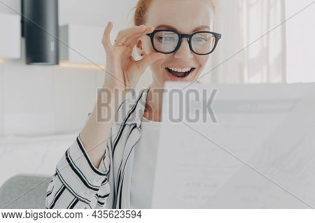 Positive Redhead Young Woman Smiles Broadly Wears Transparent Glasses Focused At Papers Checks Finan