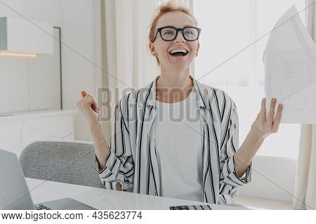 Excited Young Woman With Paper Bills In Hands Feeling Euphoric, Happy About Finally Paying Down Her