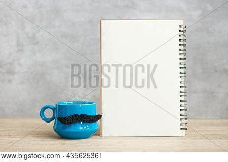 Blue Coffee Cup Or Tea Mug With Black Mustache Decor And Empty Paper Notepad Or Calendar On Table. B
