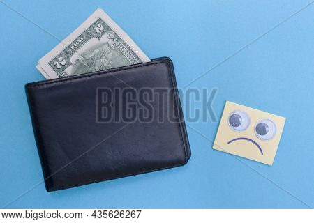 Two Dollars Are In The Wallet. Sad Emoticon Looks At The Wallet. Blue Background. Bankrupt. Money Is