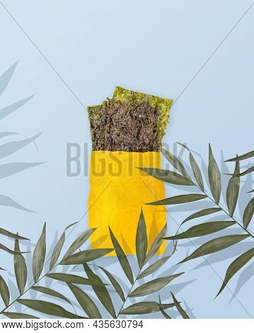 Natural Dried Seaweed Snack In A Yellow Paper Bag With Palm Leaves On A Blue Background With Copy Sp